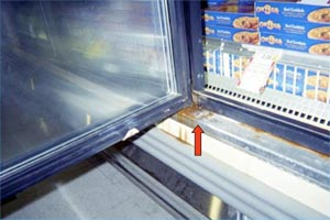 An open glass door in the freezer section of a grocery store with an arrow pointing to rust.