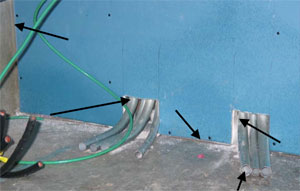A blue wall with two sections at the base where gray tubes pass through. Black arrows point to various locations where there is an air leakage.